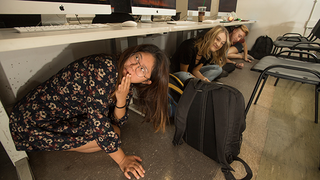 Students take cover under desks during Lauren Furey's Magazine Journalism class in Building 1 as part of the Great California Shake Out earthquake drill.