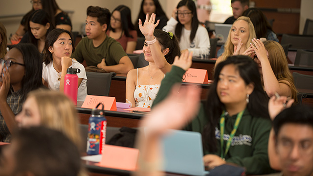 students in class with female raising hand