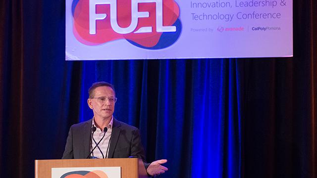 Dean Erik Rolland speaking at conference.