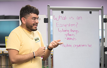 Martin Rios, a botany major and a Prete Fellow, talks with students at Armstrong Elementary School.