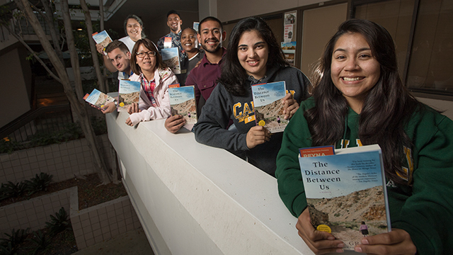 Students with The Distance Between Us book.