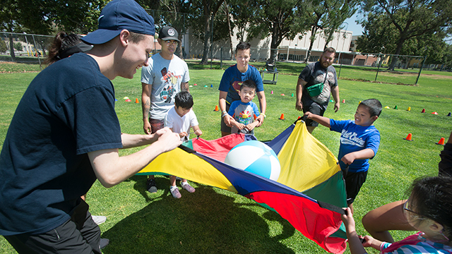 Children use a Parachute during motor development class