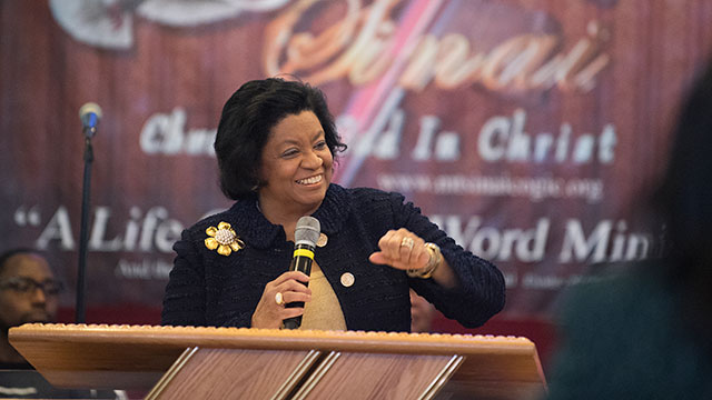President Coley smiles at a pulpit while speaking during Super Sunday.