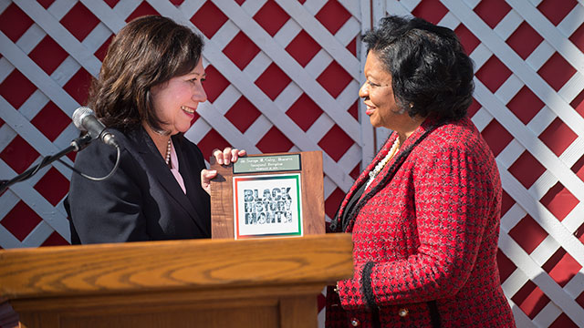 Hilda Solis presents President Coley an award.