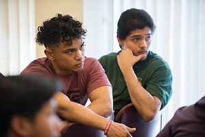 Three student sitting in a presentation.