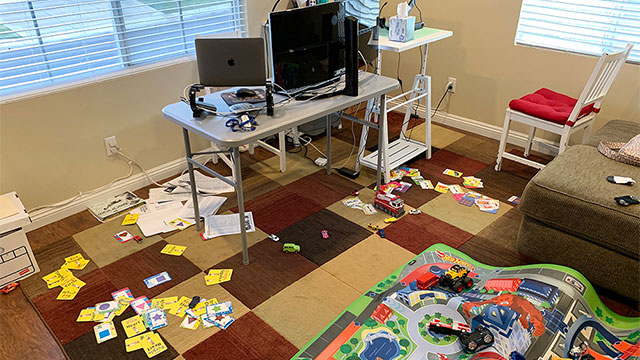 Workspace with computers and child's rug.