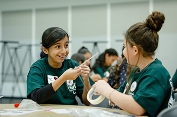Two young girls show each other their projects during introduce a girl to Engineering.