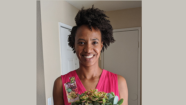 Aneika Solomon Garcia smiles holding a succulent plant.