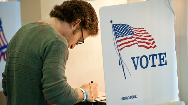 A male student stands at a voting kiosk.