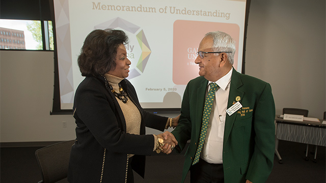 President Soraya M. Coley shakes hands with alumnus Ganpat Patel, the founder of Ganpat University in India.