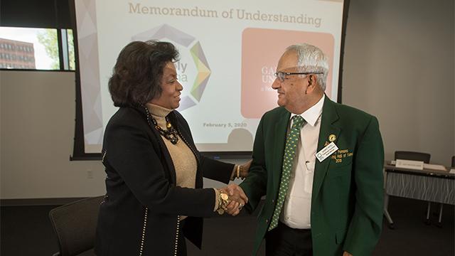 President Soraya M. Coley shakes hands with alumnus Ganpat Patel, the founder of Ganpat University in India.