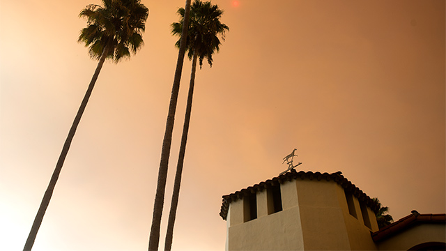 Smoke in the sky behind the old stables and palm trees.