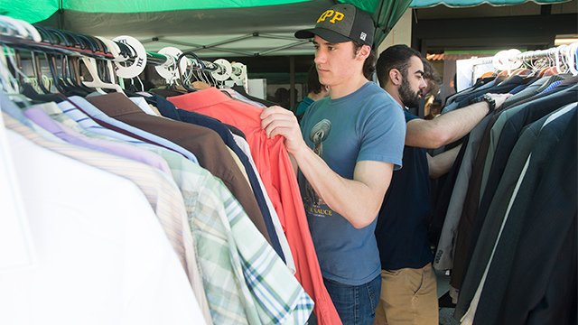A student goes through a rack of clothing at the Career Center's Clothes Closet.