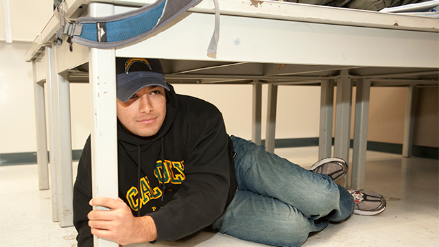 A male student under a table during a Great Shake Out Drill