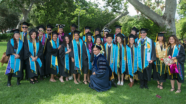 Students from the College of Science post with Steve Alas during the 2019 commencement cermonies.